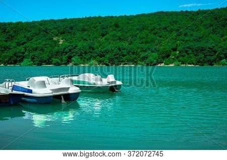 Row Of White Catamaran Stands On The Lake. Catamaran Near The Pier In Sunny Weather Against The Back