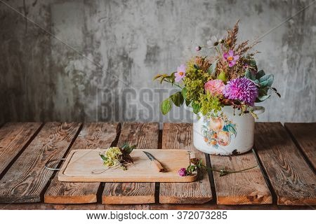 An Ancient Pot With A Composition Of Flowers On A Wooden Rustic Table Against A Concrete Wall. Conce