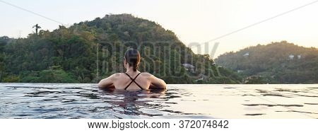 Panoramic View Of Girl In Outdoor Swimming Pool Against Forestry Hills Sunlight Closeup