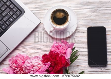 Flat Lay Womens Office Desk. Female Workspace With Laptop, Pink Peonies Bouquet And Coffee On White