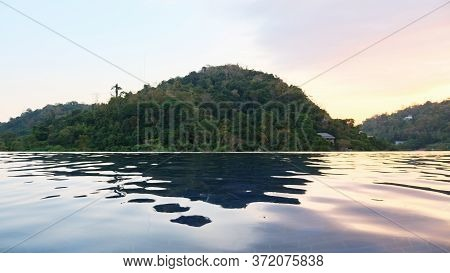 Hotel Outdoor Blue Swimming Pool Against Green Forestry Hills At Sunset