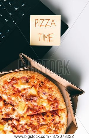Pizza In Box, Laptop And Sticker With Text Pizza Time On Desk In Office. Concept Of Food Or Pizza De