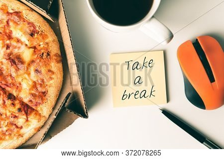Pizza In Box, Cup Of Coffee, Laptop, Computer Mouse, Pen And Sticker With Text Take A Break On Desk