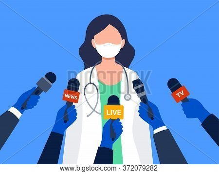 Live Report, Live News Concept. A Female Medical Worker Giving An Interview. Many Hands Of Journalis