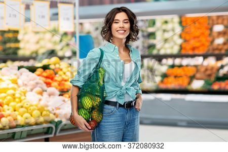 sustainability, food shopping and eco friendly concept - happy smiling woman in turquoise shirt and jeans with reusable net bag with fruits and vegetables over grocery store or supermarket background