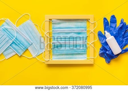 Blue Latex Gloves And Disposable Masks With Hand Sanitizers On Yellow Pattern Texture Of Crumpled Pa