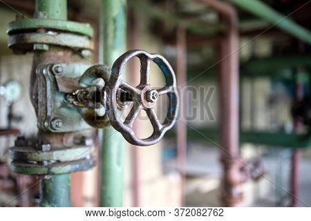 Industrial Pipeline Flanges Hand Wheel And Valve Close Up, Blur Industrial Pipelines Background. Old