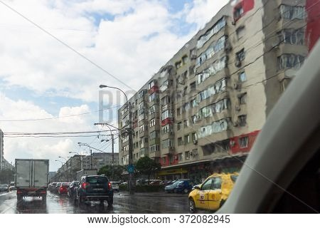 Traffic In Cloudy Rainy Day With Road View Through Car Front Window In Bucharest, Romania, 2020
