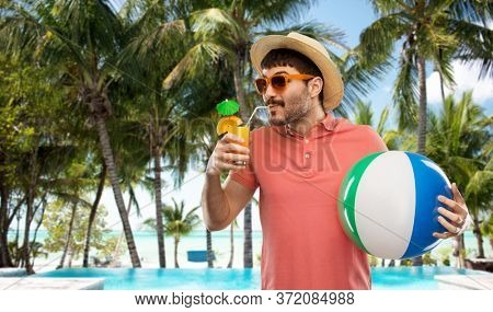 summer holidays, vacation and travel concept - happy man in sunglasses and straw hat with orange juice cocktail and inflatable beach ball on tropical beach background in french polynesia