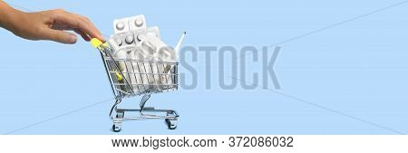 A Variety Of Pills And Medicine In Blister Packs In A Mini Shopping Trolley Or Cart And Girl's Hand
