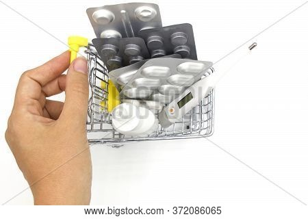 Woman Hand Holding A Mini Shopping Basket Full Of Pills, Medicine And Thermometer At The Farmacy Sto