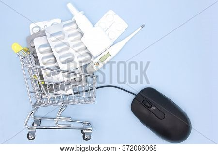 Medicines In Shopping Cart In Drugstore With Mouse To Online Order On Blue Background. Online Pharma