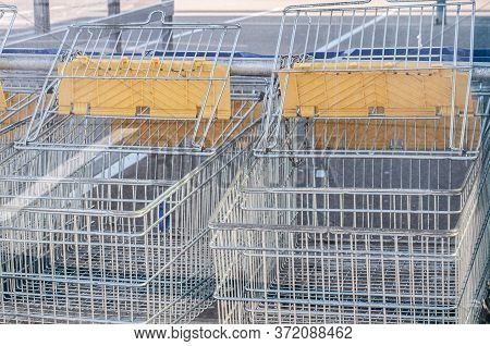 Close-up Of Shopping Carts At The Parking Lot Of A Mall Fixed With Metal Chains