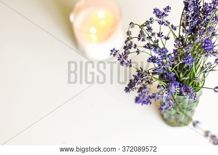 Scented Candle And Lavender Flowers On White Coffee Table In Home Interior