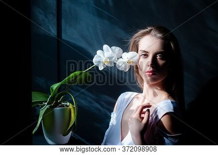 Beautiful Woman With Flower Near The Face On Black Background. Woman With Orchid. Cosmetology, Beaut