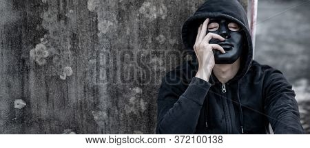 Mystery Man In Black Mask With Hoodie Jacket Sitting On Abandoned Building Feeling Tired And Stresse