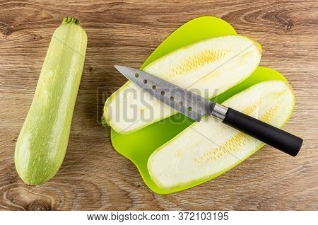 Whole Squash Marrow, Halves Of Squash Marrow And Kitchen Knife On Green Plastic Cutting Board On Woo
