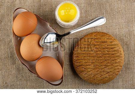 Brown Unpeeled Boiled Eggs In White Bowl, Teaspoon, Salt Shaker, Rye Flapjack On Burlap. Top View