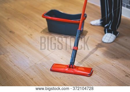 Woman Cleaning Floor Of Living Room By Mob.