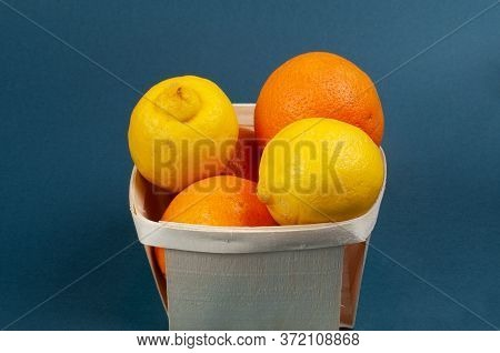 Mixed Citrus Fruits In A Wooden Basket On A Blue Background