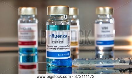 Vials Of Influenza Vaccine. Ottles With A Syringe On Black Table And Stainless Steel Background.