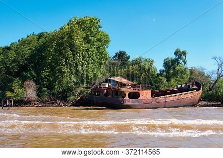 Tigra Delta In Argentina, River System Of The Parana Delta. Lush Vegetation And Old Abandoned Hull O