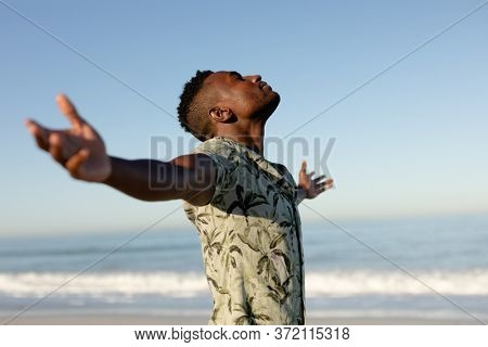 Attractive African American man enjoying free time on beach on a sunny day, wearing a Hawaiian shirt, sun shining on his face with his arms outstretched.