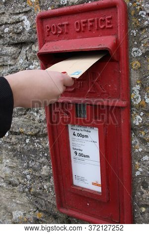 Someone Posting A Letter In A Royal Mail Post Box In The Wall In Oxfordshire In The Uk On 28th Octob