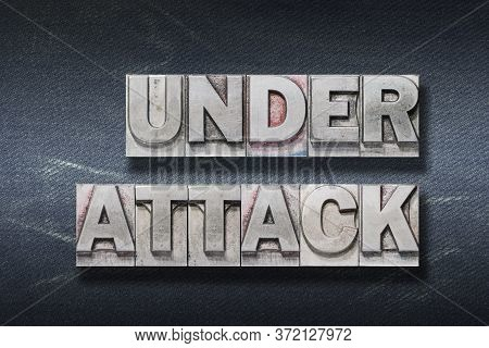 Under Attack Phrase Made From Metallic Letterpress On Dark Jeans Background