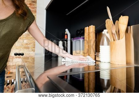 View Of Woman Holding Towel While Cleaning Kitchen Worktop