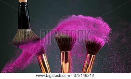 Makeup brushes touch each other on dark background and small particles of cosmetics