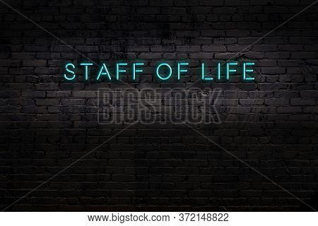 Neon Sign On Brick Wall At Night. Inscription Staff Of Life