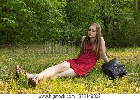 A Young Sad Long-haired Fair-haired Girl Sits In A Red Short Dress With A Backpack On The Grass In A