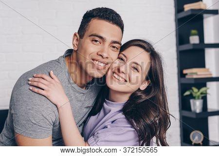 Woman Hugging Handsome Bi-racial Man In Bedroom