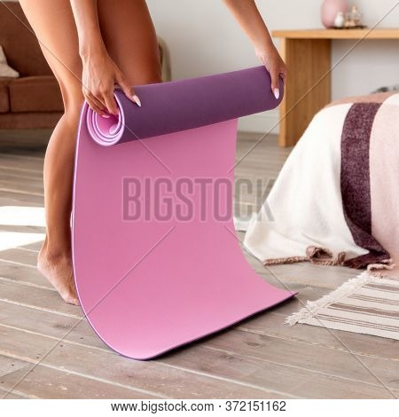 Woman is unrolling yoga mat before exercise