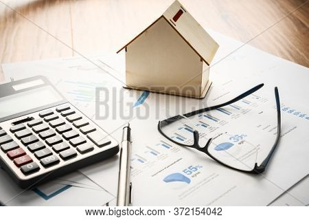 mortgage calculator with model house on desk.