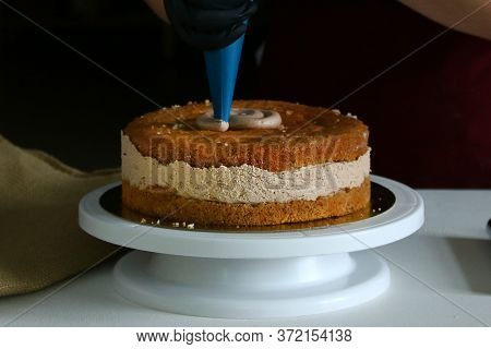 Confectioner Process Chocolate Cake On Table. The Process Of Decorating The Cake With Liquid Chocola