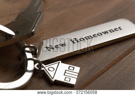 house key with new homeowner word on desk.