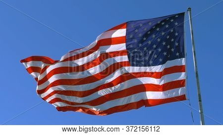 Usa Flag On Flagpole. American Flag - Symbol Of Freedom And Law In The Usa. American Flag Flies In T