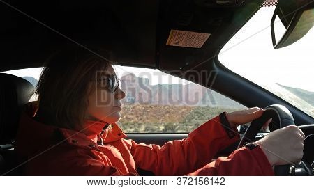 Young Woman Is Driving A Car On A Sunny Day, Outside The Window Is A Mountain Landscape The Red Rock