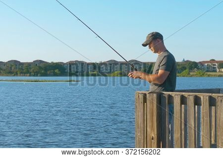 Fisherman Throws A Fishing Tackle Into The Lake From A Wooden Pier. Fishing In River. Man Fisherman