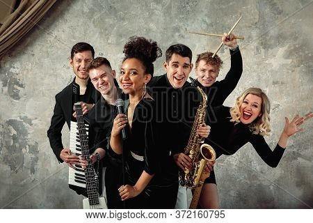 Cheerful International Music Group On A Gray Wall Background, A Group Of Musicians Posing On Camera