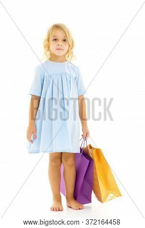 A Cheerful Little Girl Is Shopping In A Store With Large, Multi-colored Paper Bags. The Concept Of H