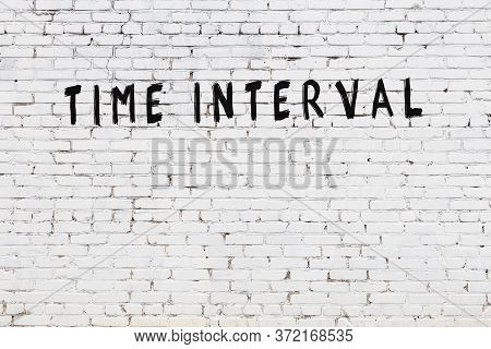 Word Time Interval Written With Black Paint On White Brick Wall.