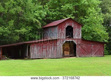 Red, Weathered, Wooden Barn Stands On A Small Farm In Arkansas.  Loft Is Open.  It Stands At The Edg