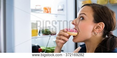 Hungry Young Woman Eating Donuts Near Fridge