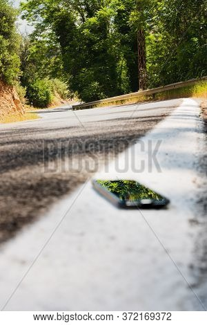 Vertical Color Image With A Floor Angle View Of A Forgotten Or Lost Smartphone On The Roadside On Th