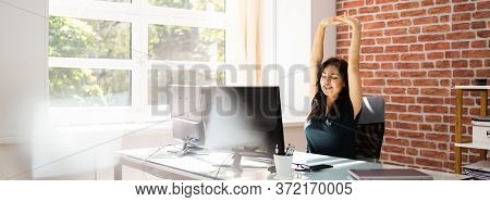 Desk Stretch Exercise. Woman Stretching At Work In Office