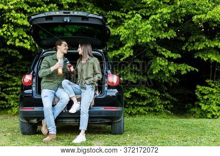 Young Couple Sitting Together In Car Trunk And Drinking Beer In Forest Outdoors
