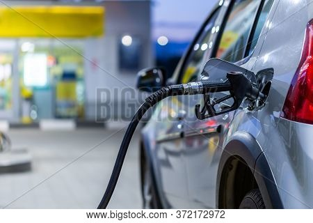 Silver Metallic Color Car Refueling On Night Gas Station - Close-up With Selective Focus And Blurry